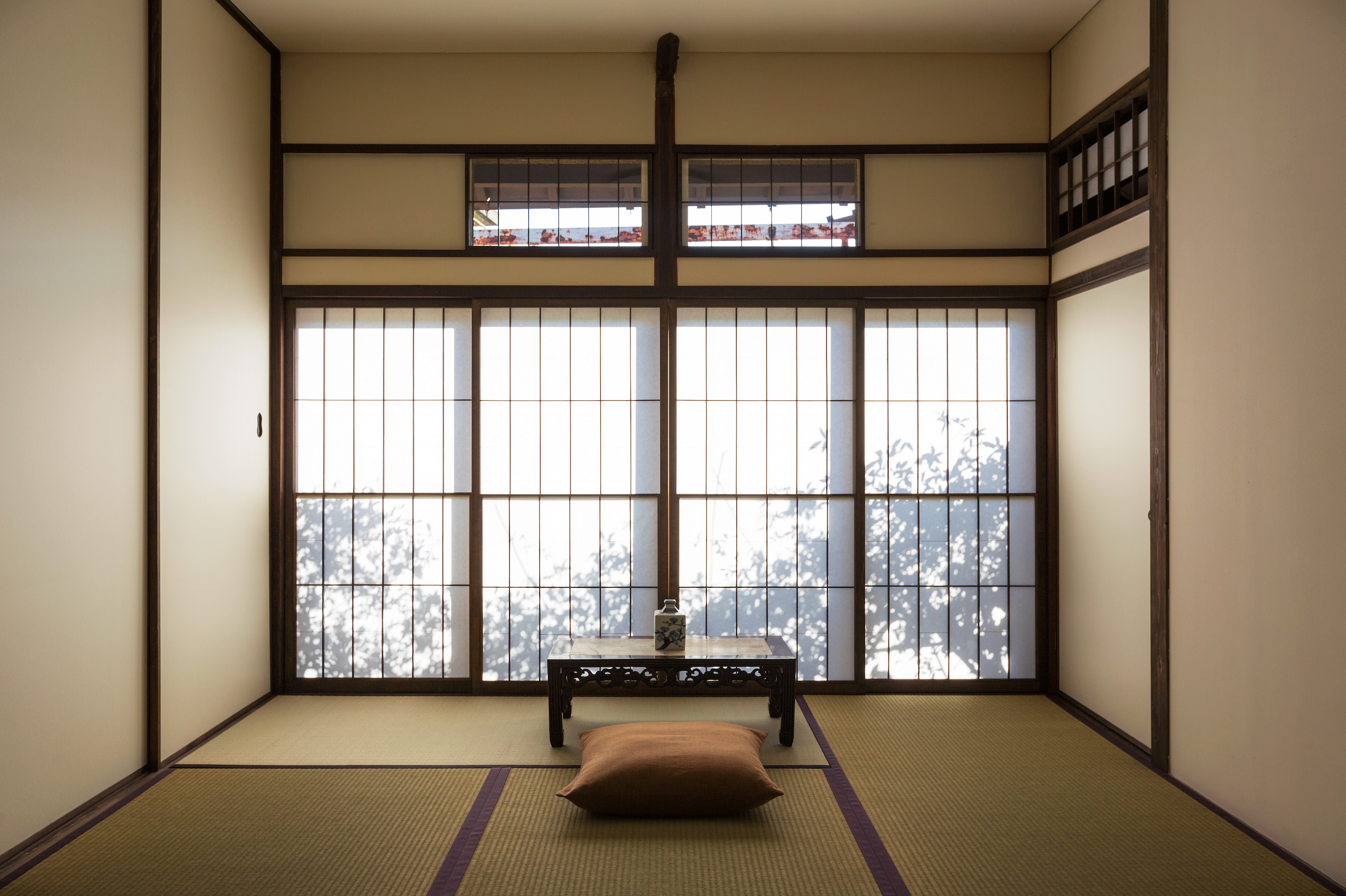 6 tatami-mat Japanese room with a stunning view of the hedgerows illuminated by sunrise.